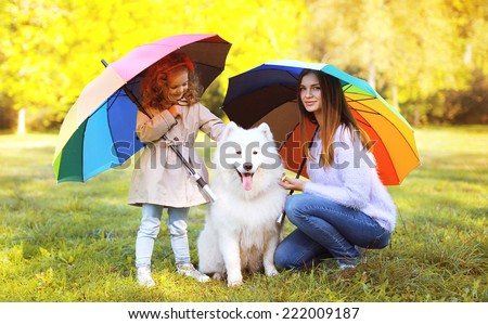 Family, leisure, weather and people concept - mother with child and dog walks with colorful umbrellas in sunny autumn day - stock photo