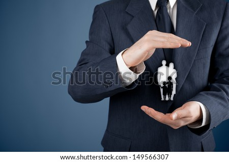 Family life insurance, family services, family policy and supporting families concepts. Businessman with protective gesture and silhouette representing young family. - stock photo
