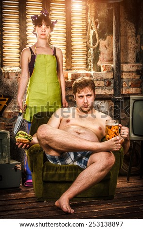 Family Life. Portrait of husband and wife in a poor slums room. - stock photo