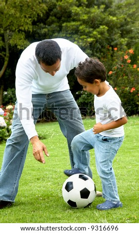 family lifestyle portrait of a dad with his son playing football - stock photo