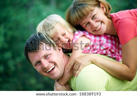 family lifestyle portrait of a mum and dad with their child having good time in the green  park - stock photo