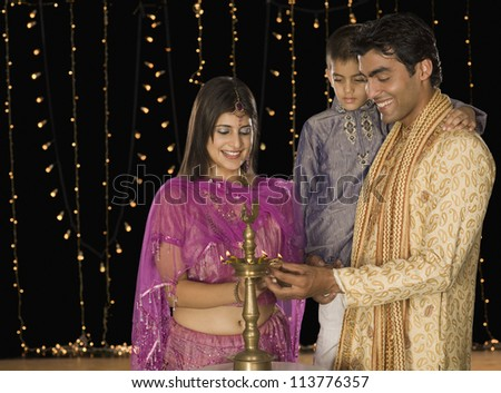 Family lighting oil lamp on Diwali festival - stock photo