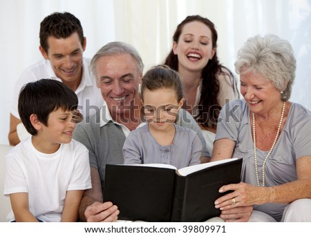Family looking at a photograph album at home - stock photo