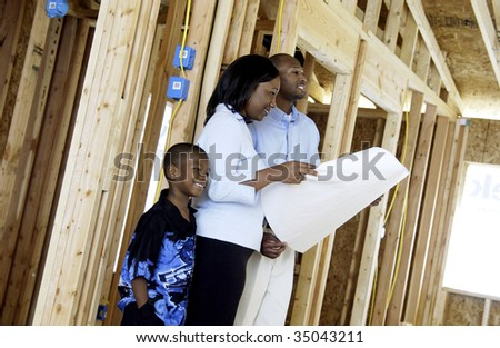family looking at house blueprints - stock photo