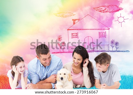 Family looking at puppy while lying against green grass under blue sky - stock photo