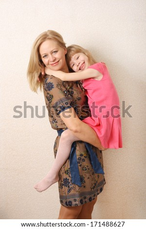 Family love happy blond mother and daughter having fun hug in dress. studio - stock photo