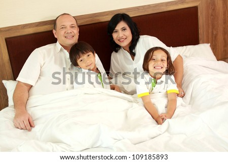 Family lying down in the bedroom - stock photo
