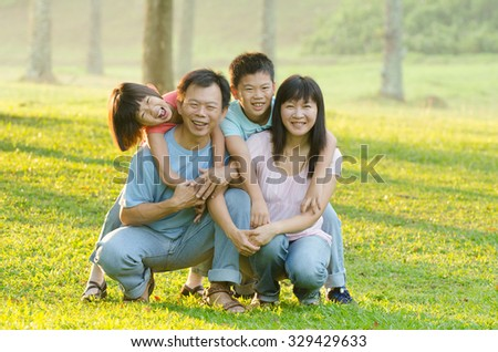 Family lying outdoors being playful and smiling, Outddor portrait - stock photo