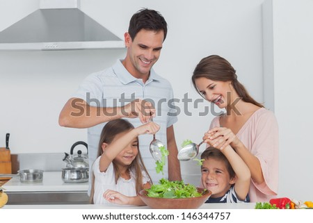 Family mixing a salad together in the kitchen - stock photo