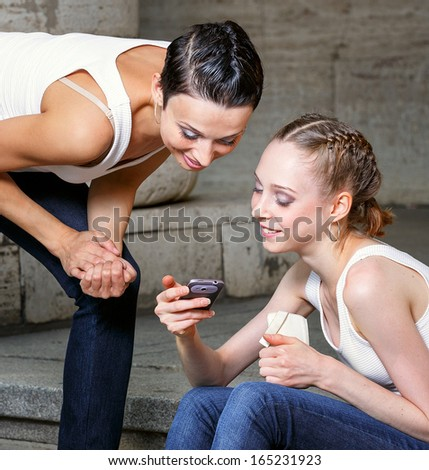 Family, mother and daughter are sitting on the steps of the library and looking at mobile phone - stock photo