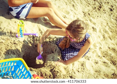 Family mother and daughter having fun on beach. Parent mom and child kid digging hole in sand. Summer vacation holidays relax. - stock photo