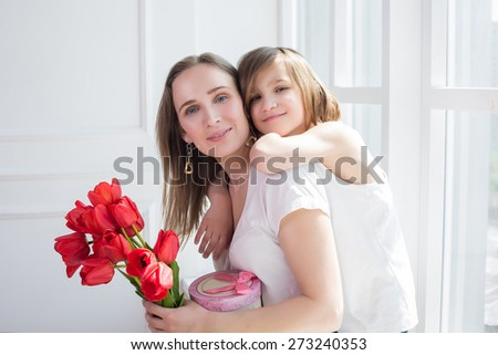 family mother and daughter portrait for mothers day in white interior with flowers  - stock photo