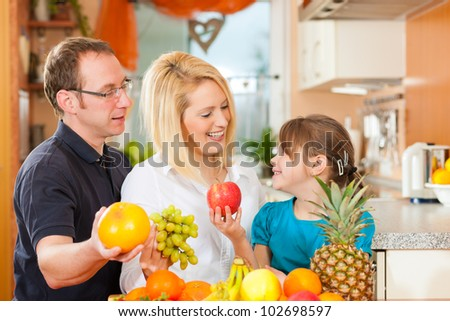 Family (mother, father and child) with lots of fruits for breakfast food, this is healthy nutrition - stock photo