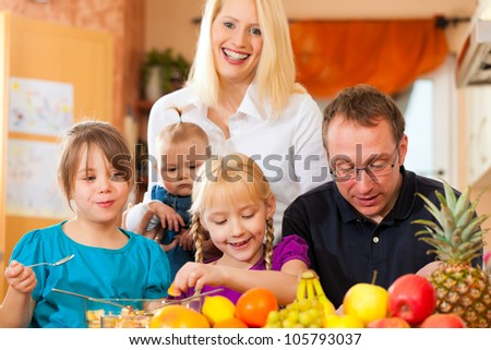 Family (mother, father and children) with lots of fruits for breakfast food, this is healthy nutrition - stock photo
