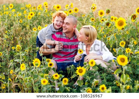 Family (mother, father, son) in sunflower field - stock photo