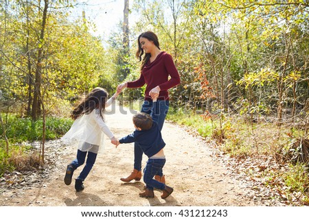 Family mother son and daughter turning circles holding hands at park - stock photo