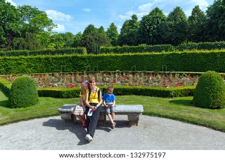 Family (mother with children) on bench in summer city park. - stock photo