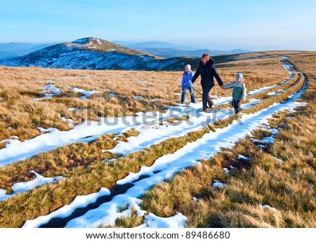 Family (mother with children) walk on autumn  mountain plateau with first winter snow - stock photo