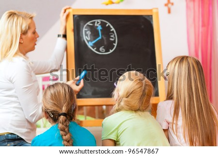 Family - mother with her daughters, all of them going to school already, the kids were thought to read the time - stock photo