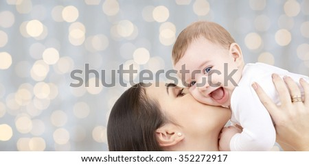 family, motherhood, children, parenthood and people concept - happy mother kissing her baby over holidays lights background - stock photo