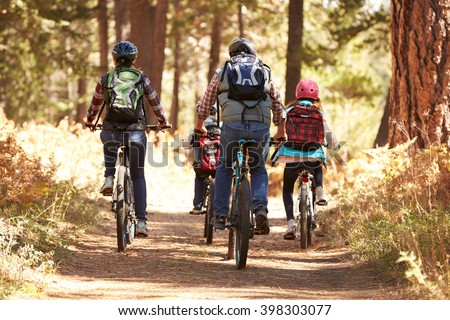 Family mountain biking on forest trail, back view - stock photo