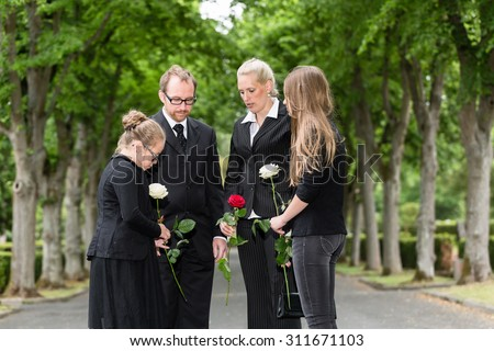 Family mourning on funeral at cemetery standing in group with flowers - stock photo