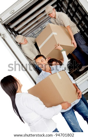 Family moving house and unloading boxes from a truck - stock photo