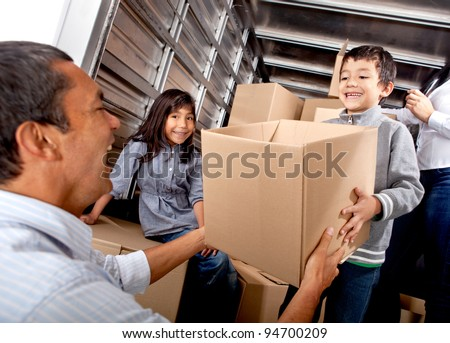 Family moving house loading a truck with boxes - stock photo