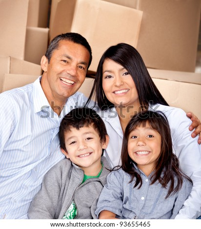 Family moving house with cardboard boxes at the background - stock photo
