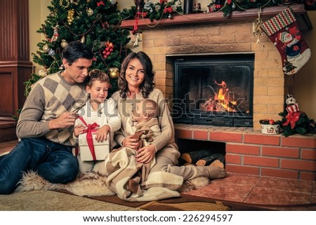 Family near fireplace in Christmas decorated house interior with gift box - stock photo