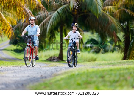 Family of father and son biking at tropical settings - stock photo