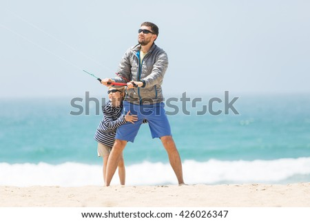 family of father and son playing with kite at the beach being active and happy enjoying vacation together, vacation and lifestyle concept - stock photo