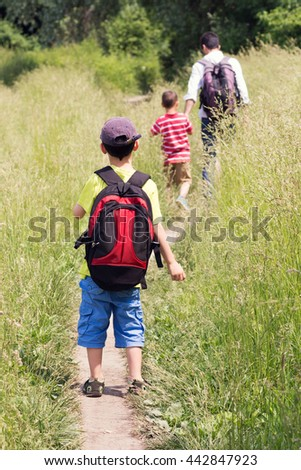 Family of father and two children walking on a path in field or meadow.  - stock photo