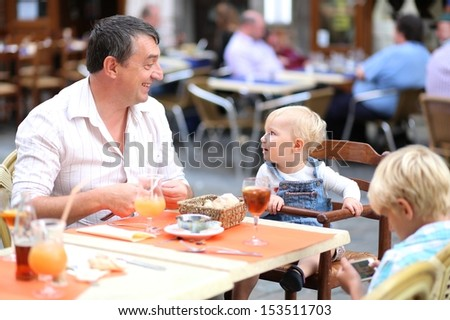 Family of father with children, teenager son and baby daughter are relaxing in cafe on a busy street in the center of the city, laughing and drinking refreshing ice tea and juice - stock photo