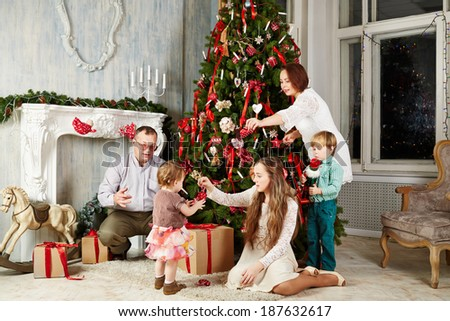 Family of five in room during decorating christmas tree, shot was taken in public rented studio - stock photo