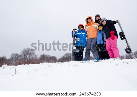 Family of five on ski holiday in mountains standing on ski slope holding equipment - stock photo