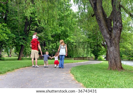 Family of five walk down a curving path at the Elizabethton Covered Bridge in Elizabethton, Tennessee.  Dad carries baby and little brother and sister hold mom and dad's hands. - stock photo