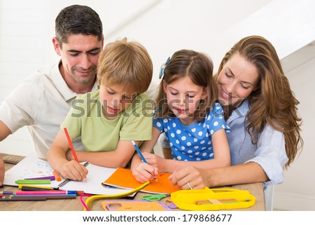 Family of four coloring together at home - stock photo