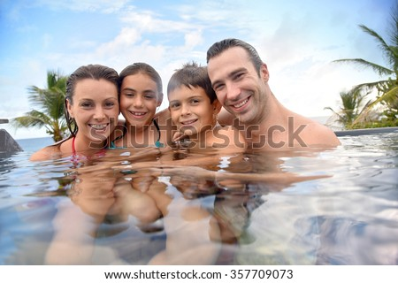 Family of four enjoying swimming-pool - stock photo