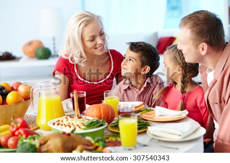 Family of four gathering at dinner table - stock photo