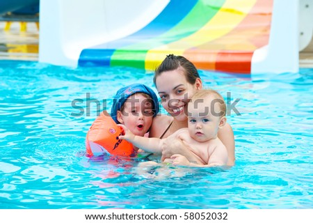 Family of four having fun in the pool - stock photo