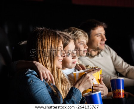 Family of four having snacks while watching movie in cinema theater - stock photo