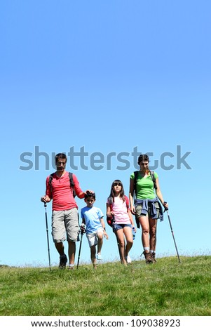 Family of four hiking in the mountain by sunny day - stock photo