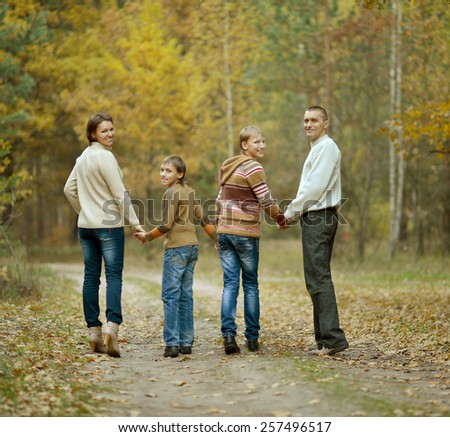 Family of four in autumn forest,back view - stock photo
