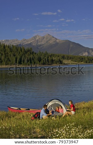 Family of four in campsite on edge of lake with mountains in the background. - stock photo