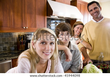 Family of four in kitchen, teenage boy frowning - stock photo