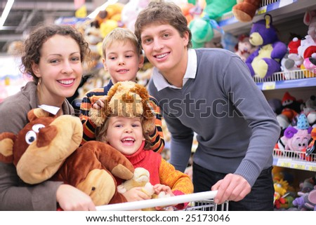 Family of four in shop with soft toys, focus on little girl - stock photo