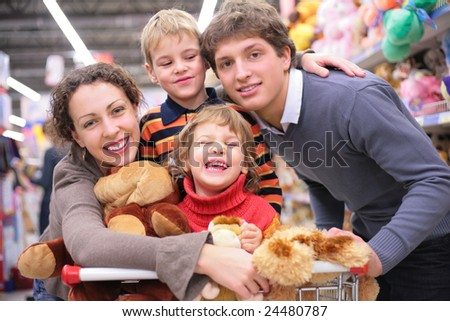Family of four in shop with toys - stock photo