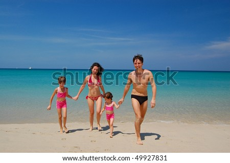 Family of four in swimming suits on tropical beach. Family vacation - stock photo
