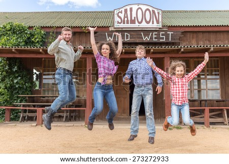 family of four jumping on background of  wild west saloon - stock photo